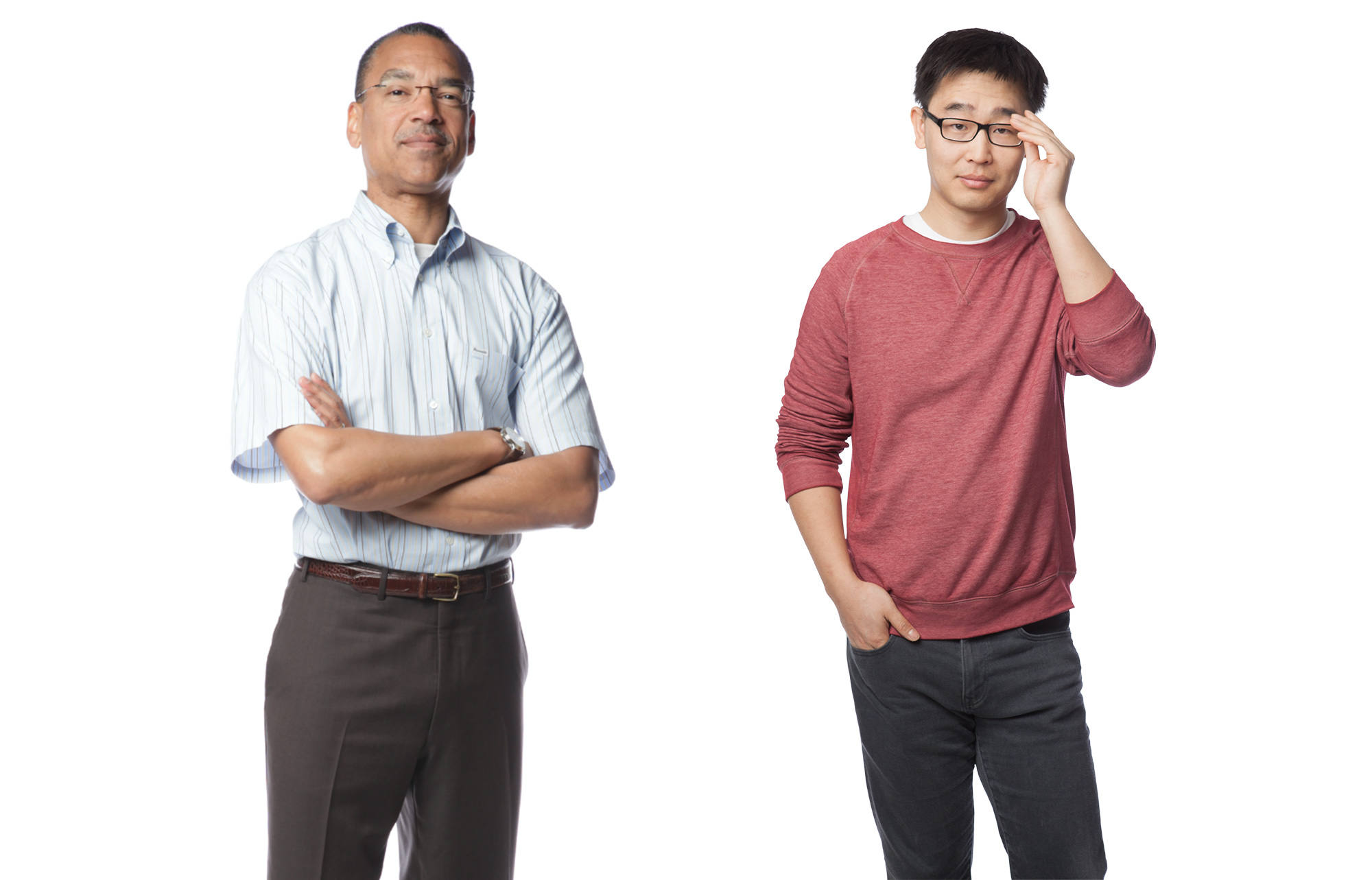 Portrait of two men. One, middle aged, looks confidently at the camera. The younger Asian man adjusts his glasses.