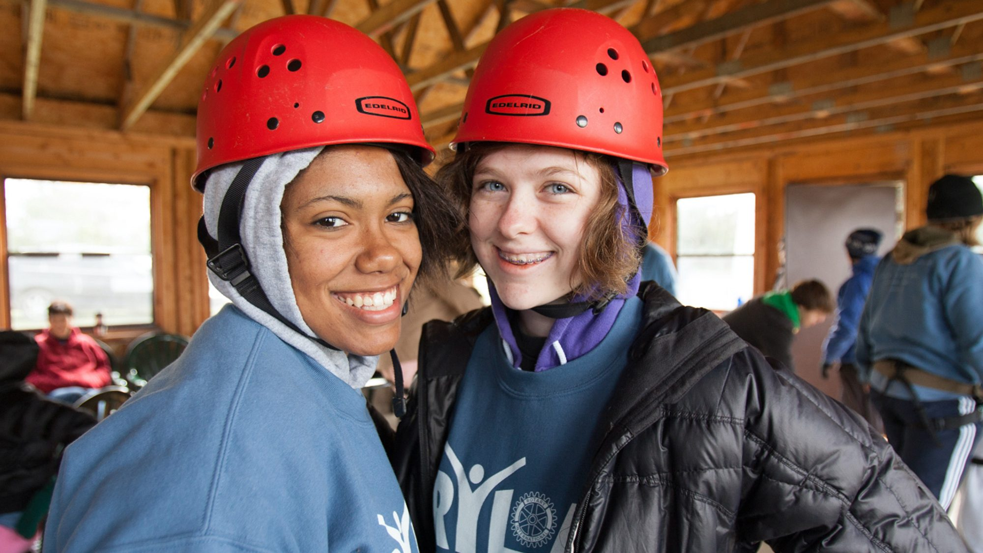 Two young women, one white one black, wearing hard hats and smiling toward the camera.