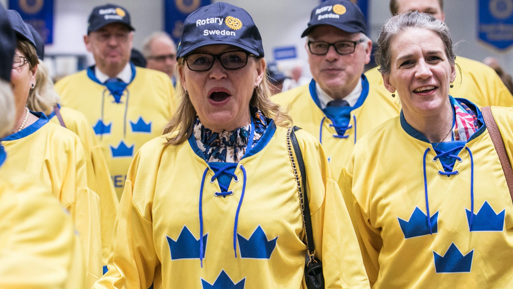 Crowd wearing yellow shirts and blue hats with Rotary Sweden logo.