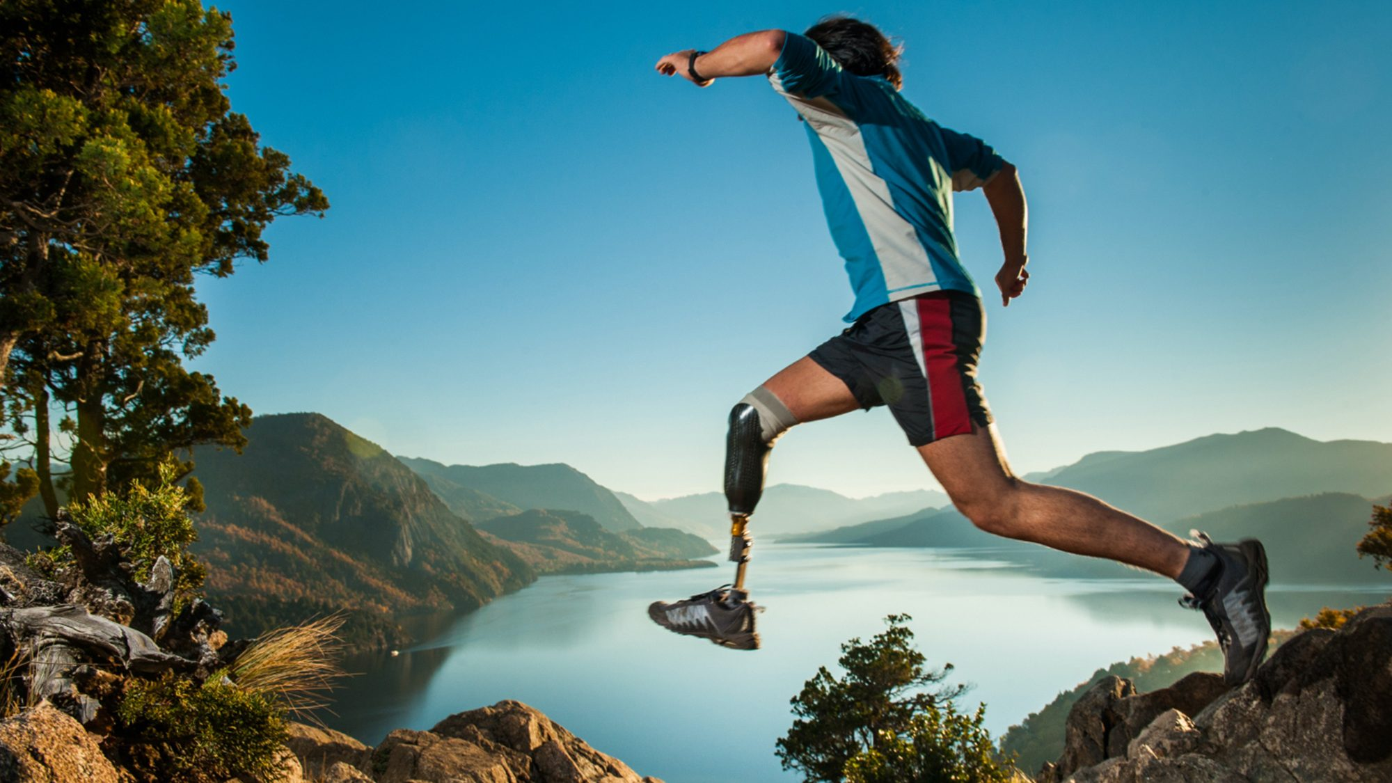 Man with a prosthetic leg running in a wild landscape.
