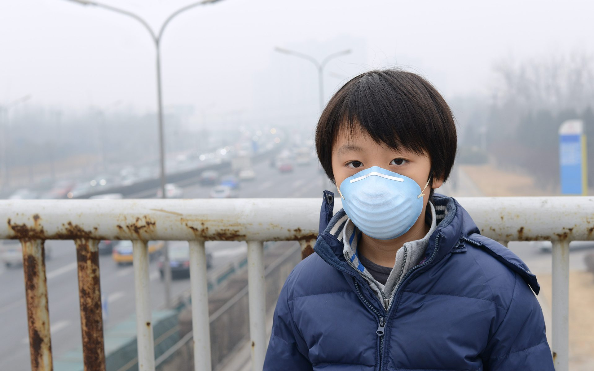 Young boy wearing filtration mask.