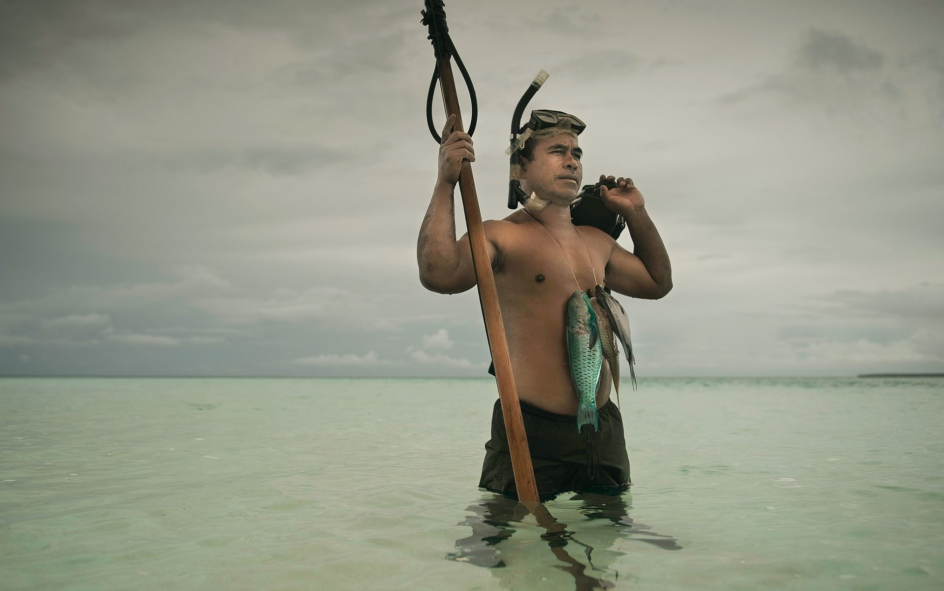 Man fishing with a snorkel and a spear.