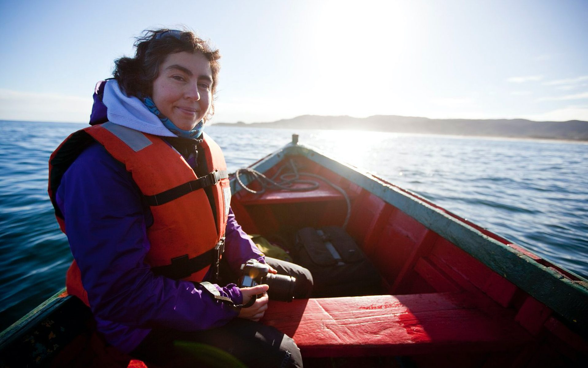 A woman in a small boat wearing a life jacket.
