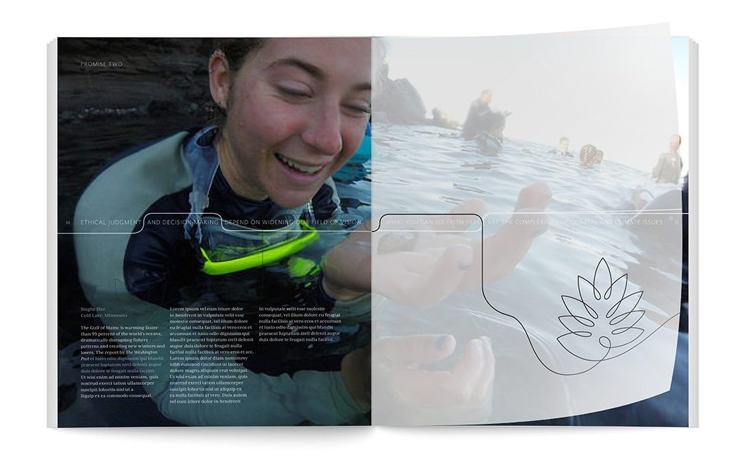 A student in a wetsuit examines a small crab.