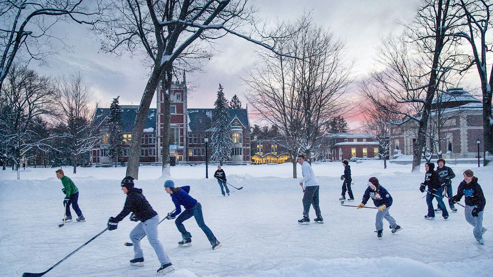 Students playing ice hockey outdoors.