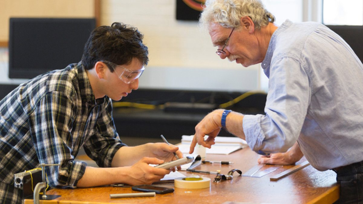 An instructor and a student examine a disassembled mechanical device.