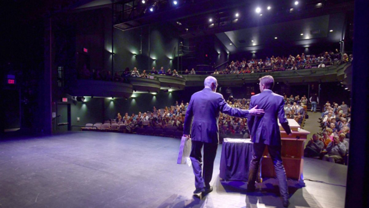 Photo of a packed auditorium from the perspective of the stage.