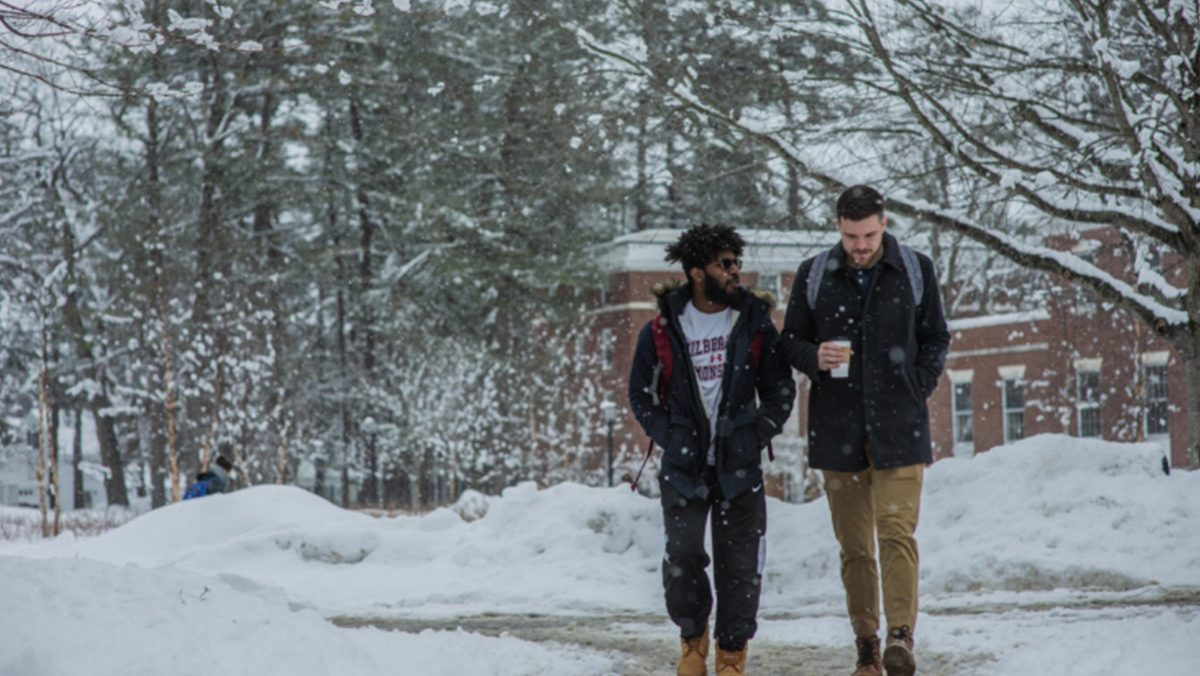 Two students walk in the snow.