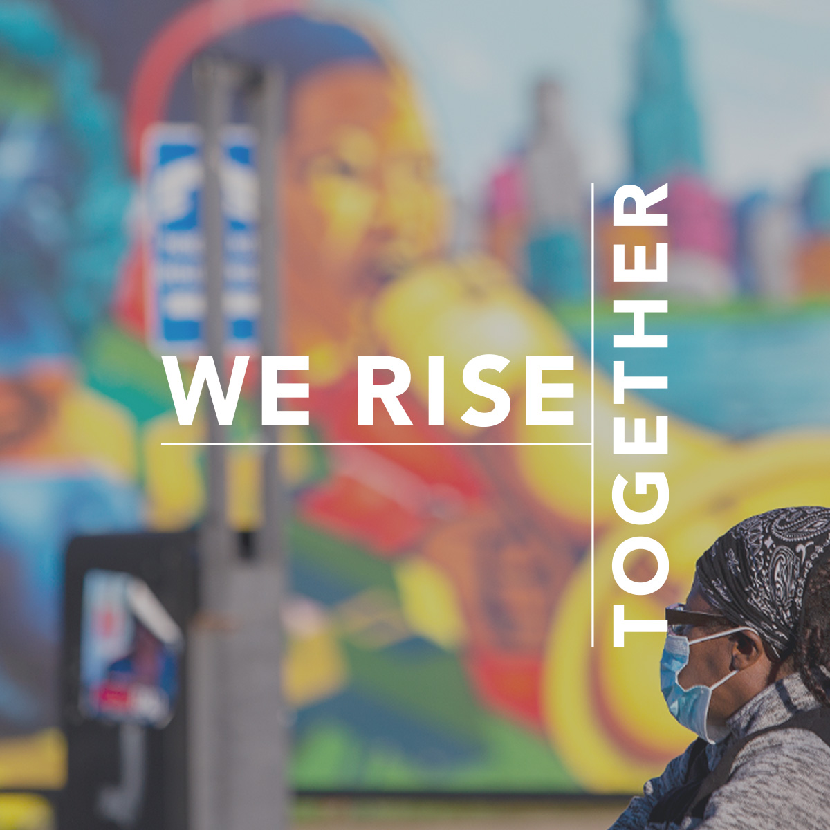 We rise together. Photo shows a black woman in a mask in front of a colorful mural.