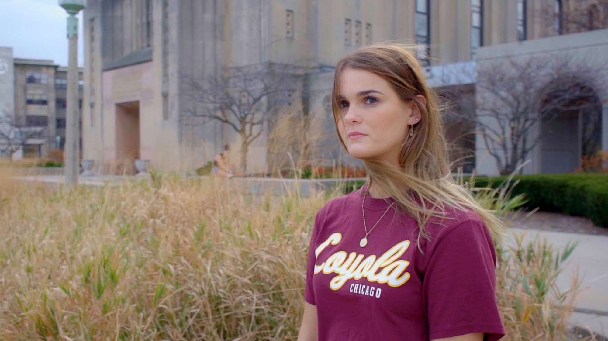 Video still — college age white woman in red Loyola tee shirt.