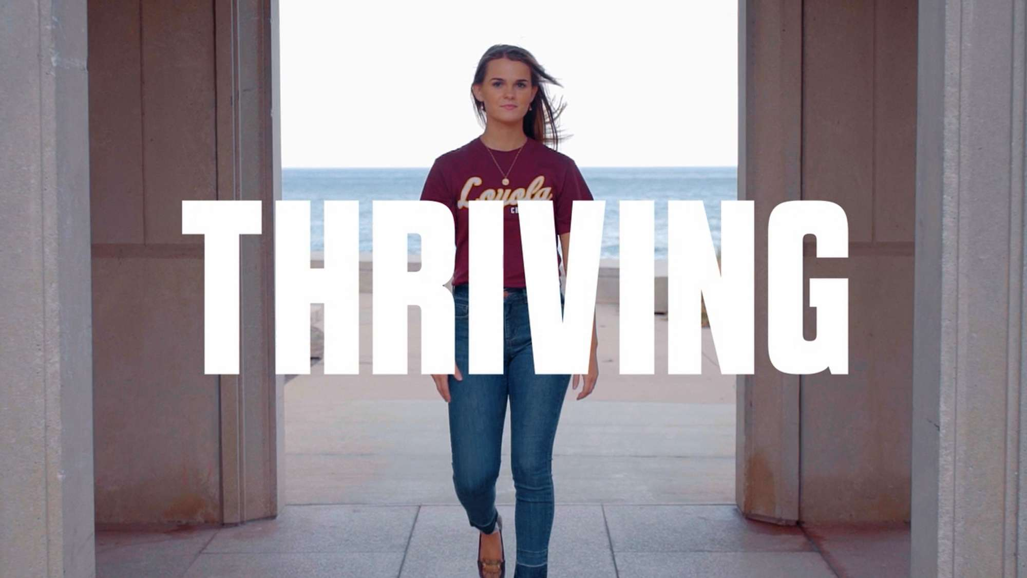 Confident college-age woman walking toward the camera. The word Thriving appears.